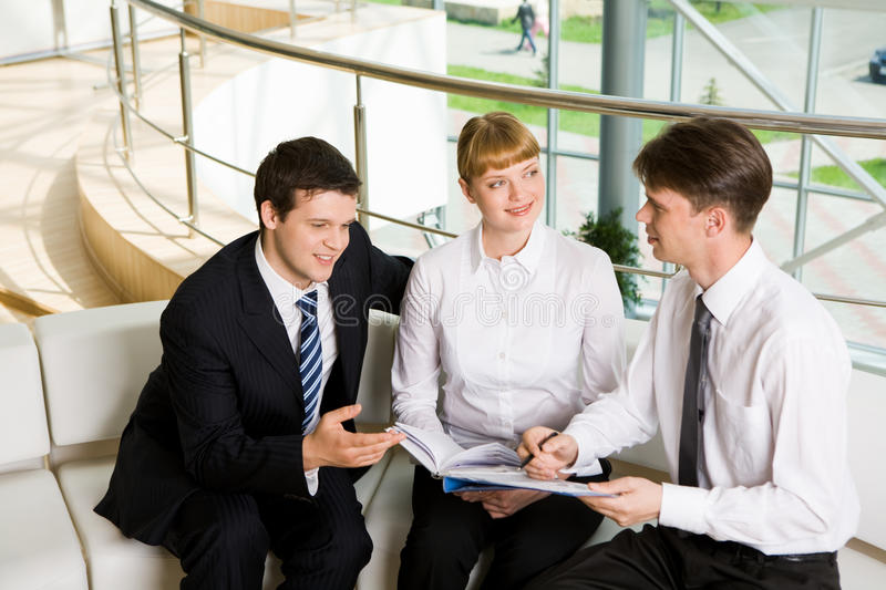 Negotiations. Photo of company of successful people planning work in office royalty free stock photography