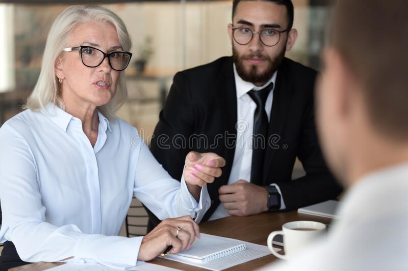 Negotiations lead by middle-aged businesswoman talking with client stock photos
