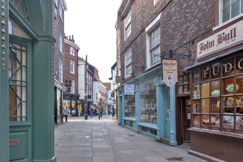 Negozi lungo la via dei portoni di Minster vicino a York Minster in distretto storico della città di York, Inghilterra, Regno Uni immagini stock