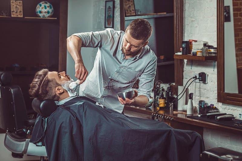 Negozio di barbiere di visita del cliente dei pantaloni a vita bassa fotografia stock