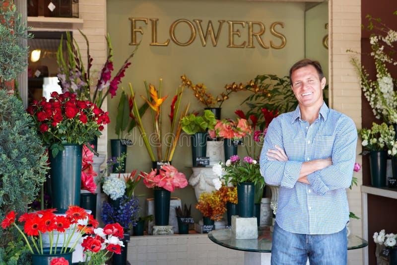 Negozio di fiore esterno diritto del fiorista maschio fotografia stock
