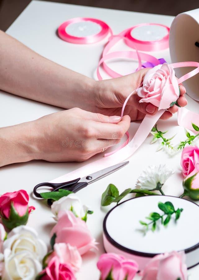 Negozio di fiore: Una ragazza fa un mazzo delle rose in una scatola rotonda Primo piano delle mani immagini stock libere da diritti