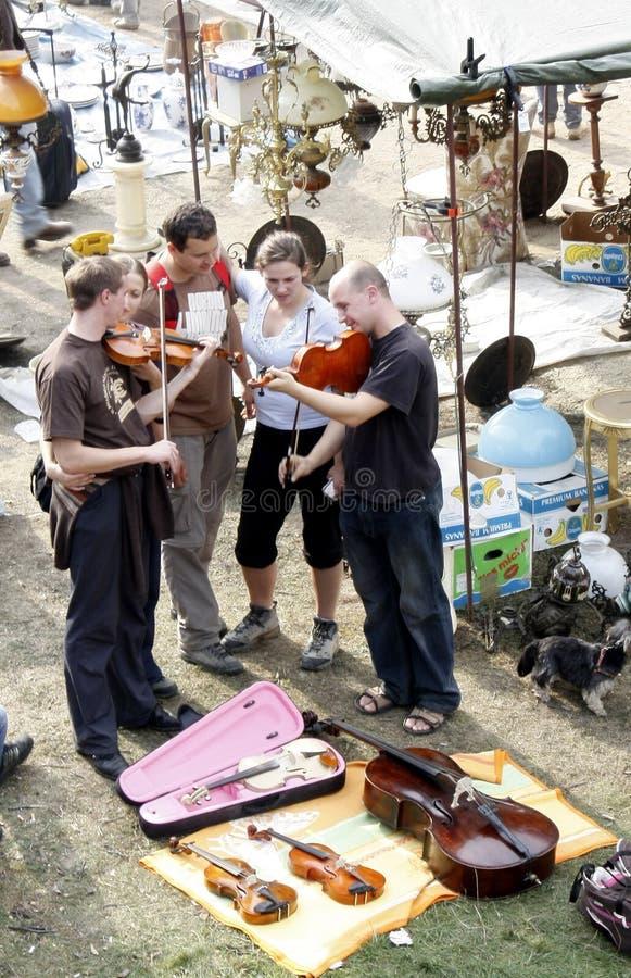 NEGRENI, RUMÄNIEN cca 2011, gruppen av unga män och kvinnor försöker till salu musikinstrument royaltyfri bild