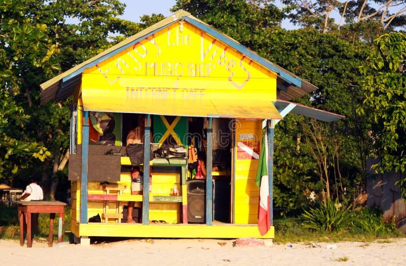 NEGRIL, JAMAICA - 24 DE MAIO 2010: Café amarelo da loja e de Internet da música na praia de Bourbon foto de stock royalty free
