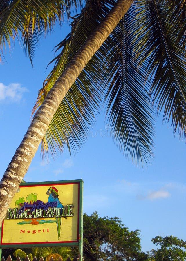 NEGRIL, JAMAICA - 24 DE MAYO 2010: Muestra de Margaritaville con la palmera en la playa de Borbón foto de archivo libre de regalías