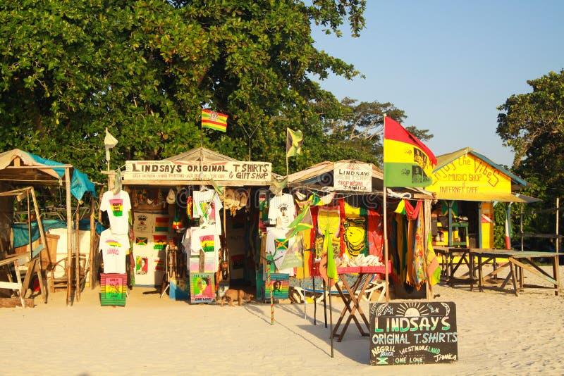 NEGRIL, JAMAICA - 24 DE MAYO 2010: Tiendas del regalo y de la artesanía en la playa de Borbón imagen de archivo