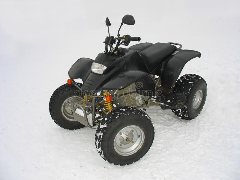 Negro de ATV todo el vehículo del terreno en la nieve blanca fotos de archivo