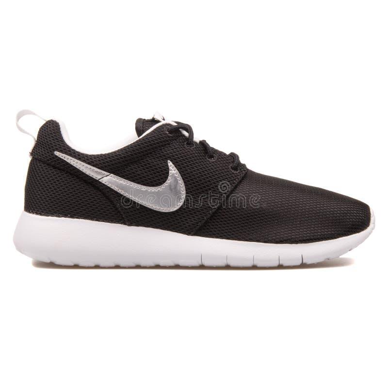 Negro de Nike Roshe One y zapatilla de deporte de la plata metalizada imagen de archivo