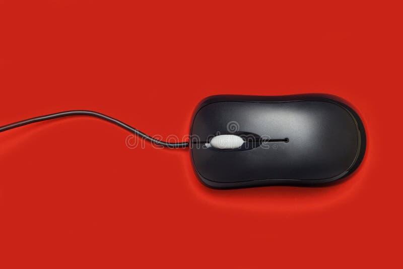 Negro del ratón del ordenador en un fondo rojo Primer imagen de archivo