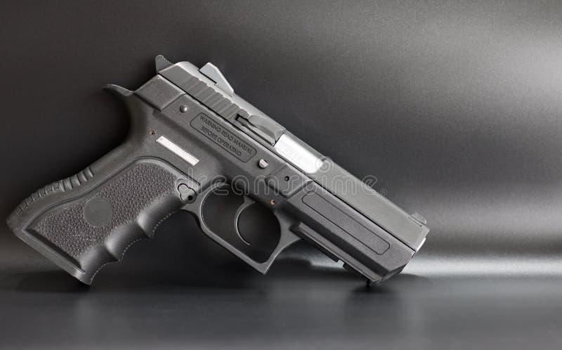 Negro pistola de 9 milímetros en un fondo gris imagen de archivo libre de regalías