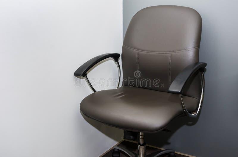 Negro, silla de la oficina contra la perspectiva de una pared blanca en la oficina imagen de archivo