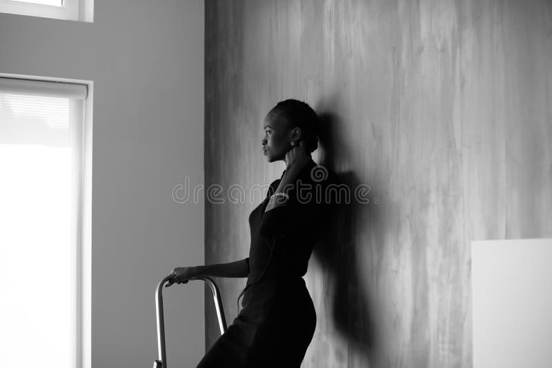 Negro-y-blanco-retrato de la mujer americana bastante africana o negra que toca su trenza gruesa en fondo oscuro del estudio imagen de archivo