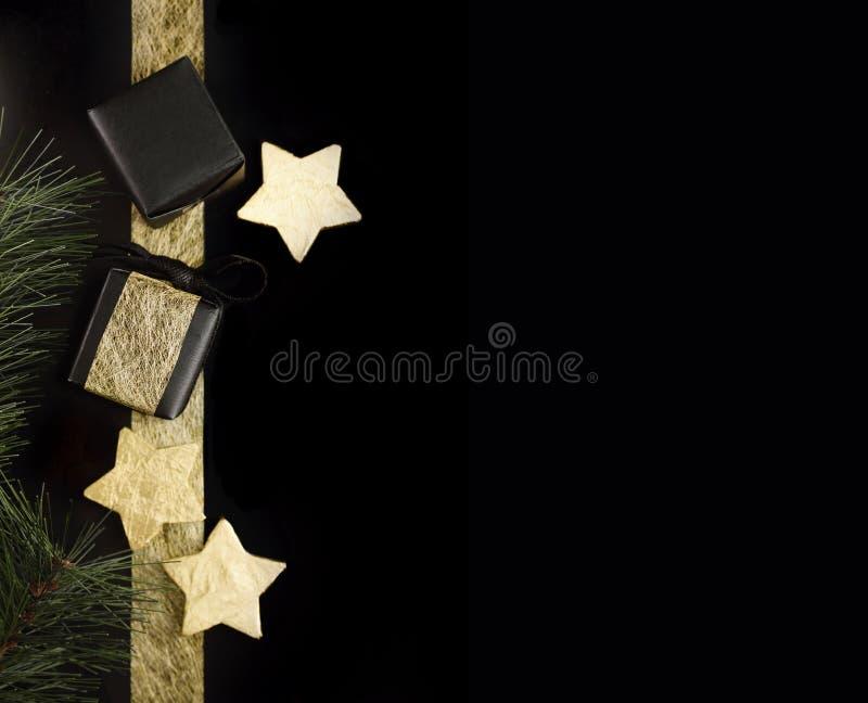Negro y regalos de la Navidad del oro con las estrellas de la hoja en fondo oscuro imagen de archivo