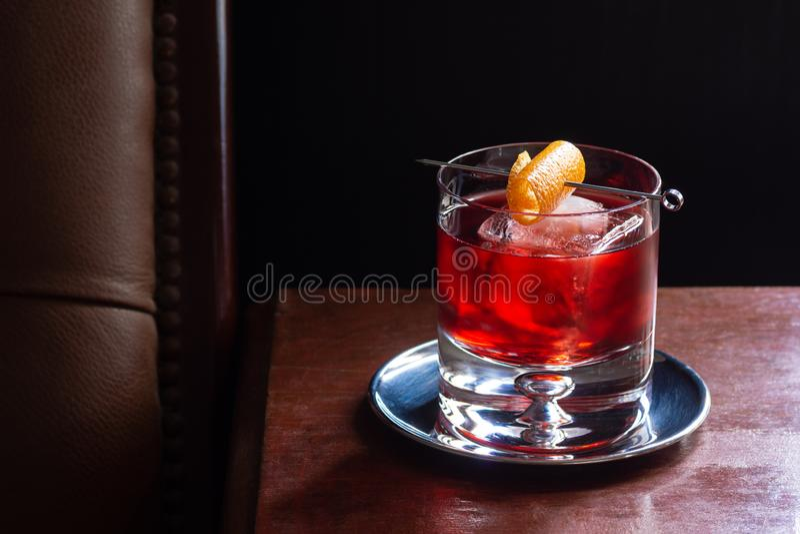 Negroni coctail med is och orange vridning i stång royaltyfria foton