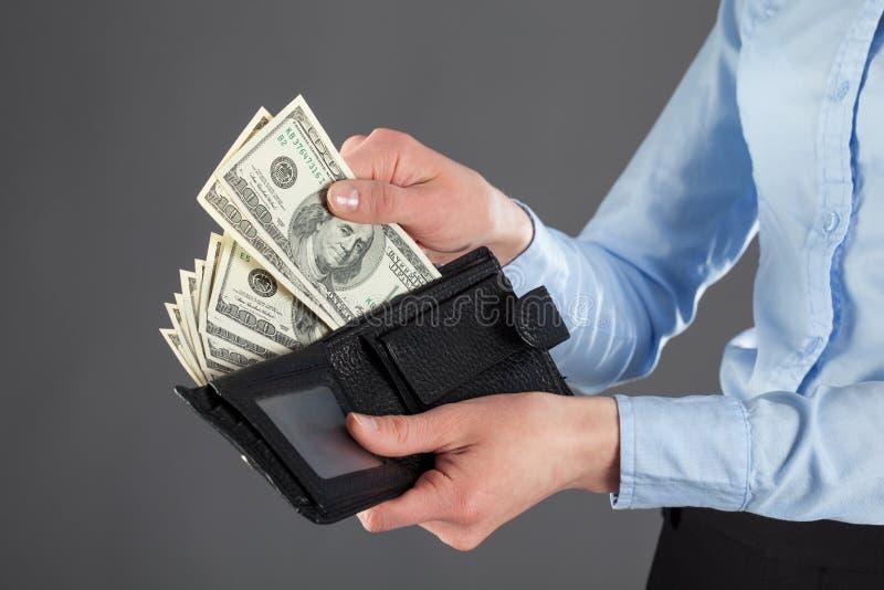 Nehmen des Geldes aus einer ledernen Geldbörse heraus stockbild