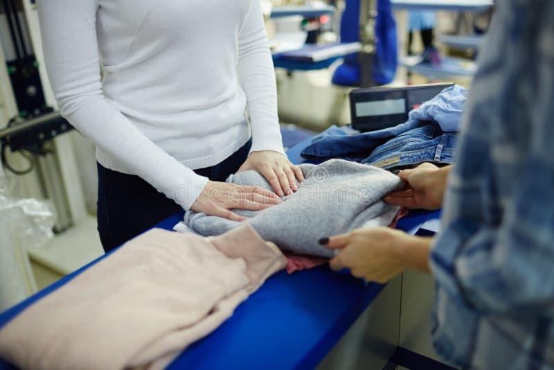 Nehmen des Pullovers von der Trockenreinigung lizenzfreie stockfotos
