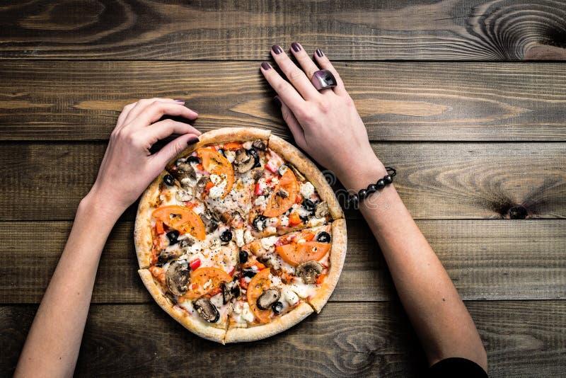 Nehmen Draufsicht der NAHAUFNAHME SEHR HEISSE GESCHNITTENE italienische Pizza mit der Hand eine Scheibe auf Holztisch mit Pilzen, lizenzfreie stockbilder