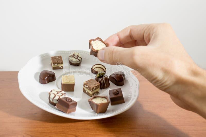 Nehmen einer Schokolade auf einer Platte auf einer Tabelle lizenzfreie stockfotos