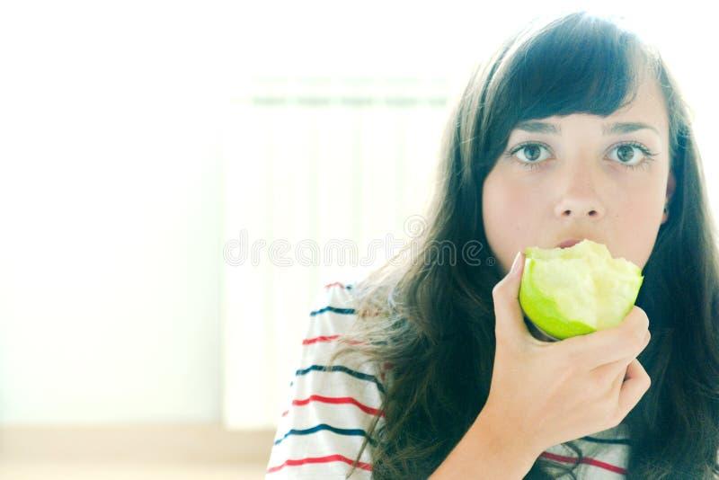 Nehmen eines Bissens eines grünen Apfels lizenzfreies stockfoto
