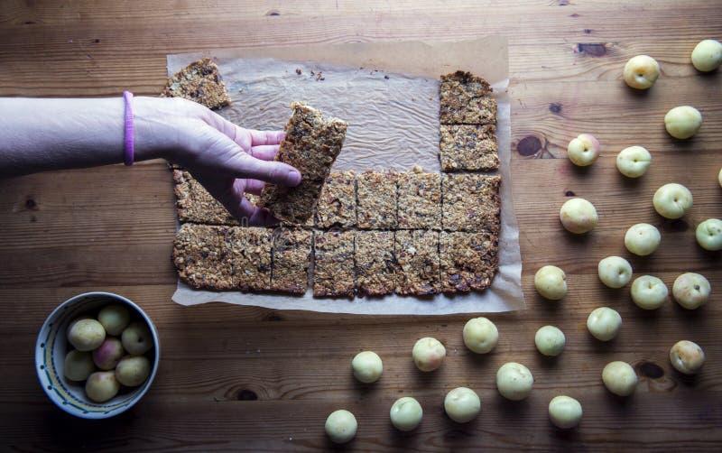 Nehmen eines selbst gemachten muesli und der Haferplätzchen mit Aprikosen stockfoto