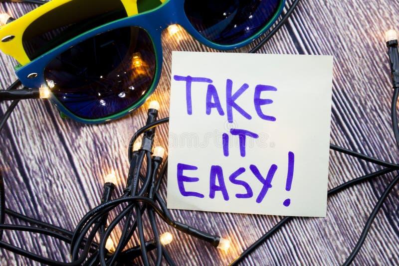 Nehmen a-handgeschriebenes Motivzitat es leicht Wörter der positiven Haltung auf dem hölzernen Hintergrund mit zwei Sonnenbrille  stockbild