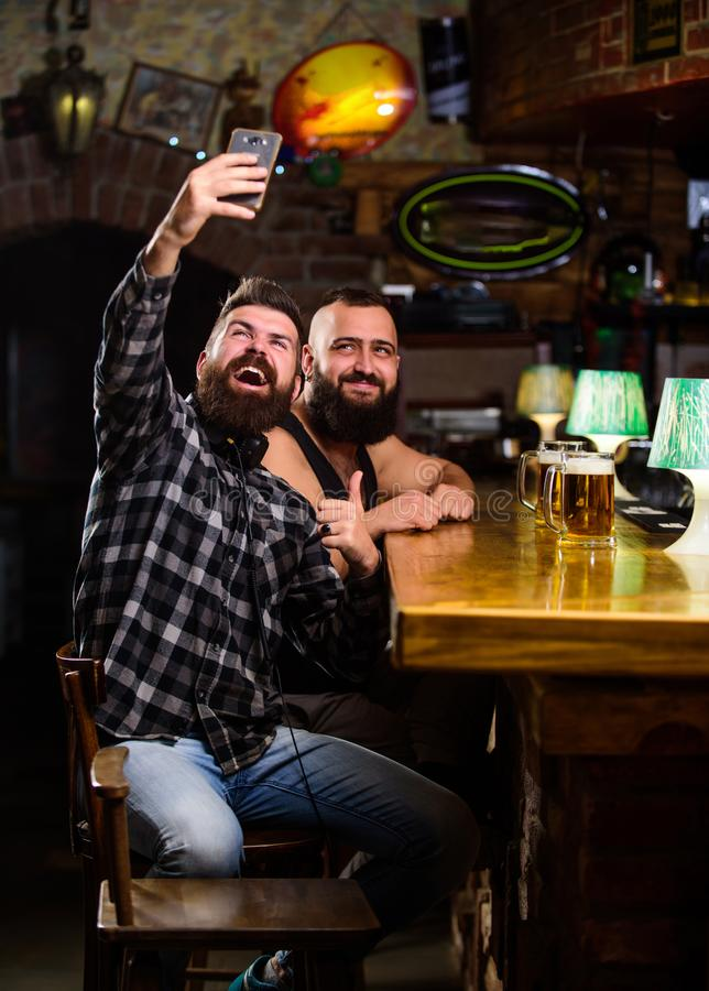 Nehmen selfie Foto, zum sich an des großen Abends in der Kneipe zu erinnern On-line-Kommunikation Hippie-Griff Smartphone des Man lizenzfreies stockbild