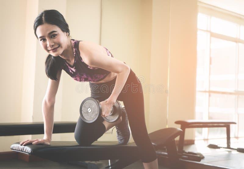 Nehmen Sie anhebenden Gewichtsdummkopf der asiatischen Frau in der Eignungsturnhalle ab stockfotografie