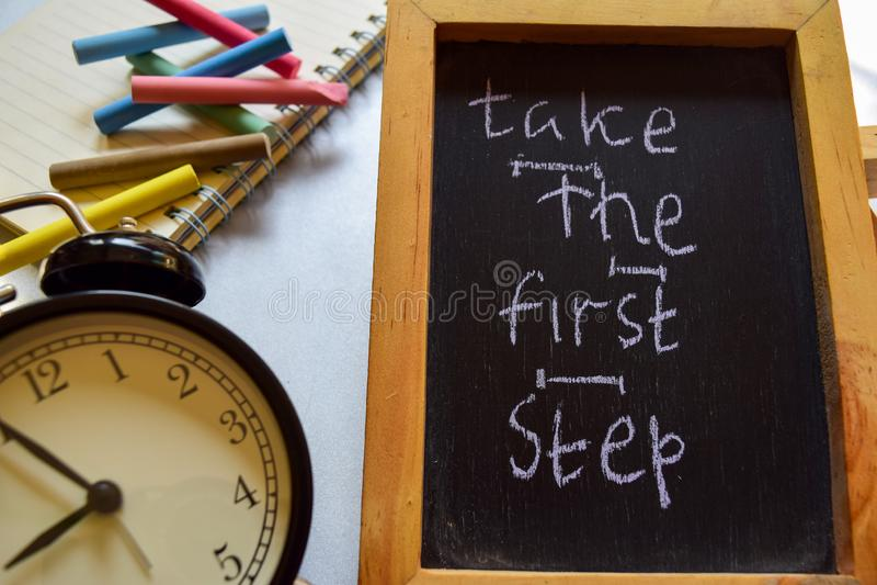Nehmen Sie der Phrase des ersten Schrittes buntes handgeschriebenes auf Tafel, Wecker mit Motivation und Bildungskonzepten lizenzfreies stockfoto