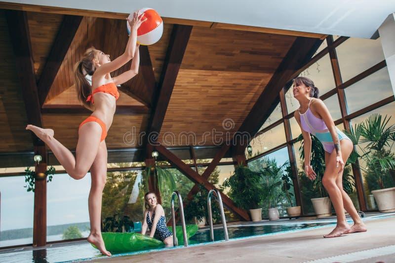 Nehmen Sie die jungen Frauen ab, die mit einem Wasserball am Innenswimmingpool spielen lizenzfreie stockfotos