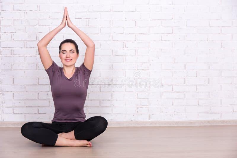 Nehmen Sie die sportliche Frau ab, die Yoga über weißer Backsteinmauer tut stockfotos