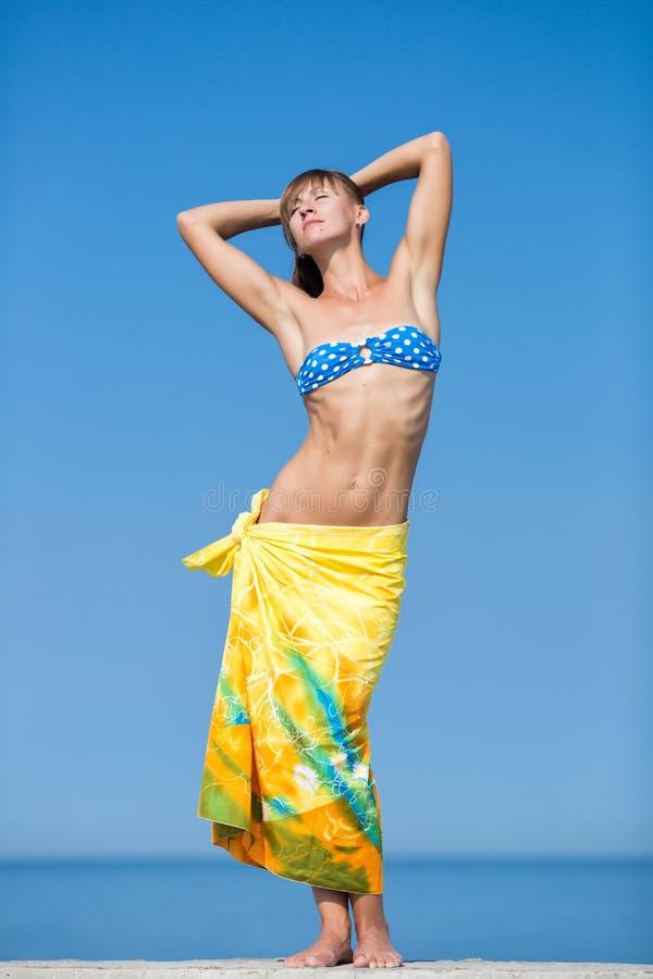Nehmen Sie großes Mädchen mit gelben Sarongen auf den Hüften ab, die mit Arme rai stehen lizenzfreie stockbilder