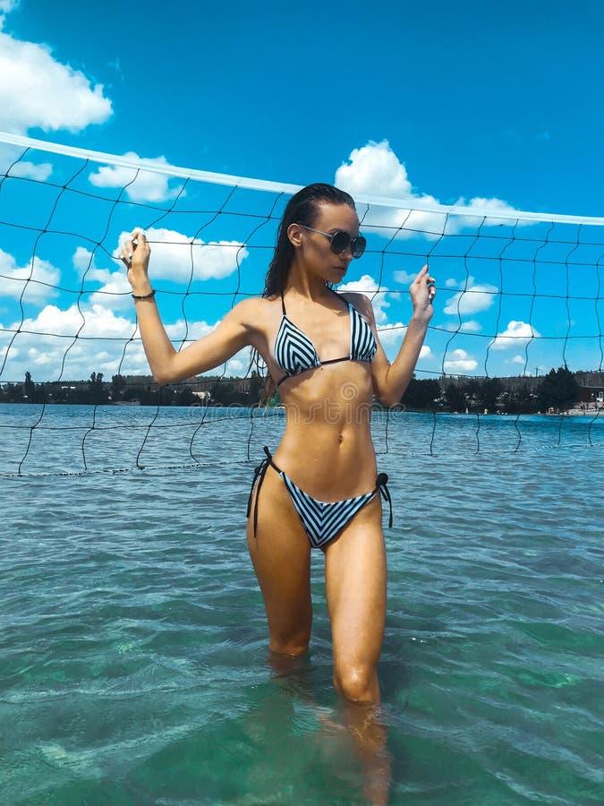 Nehmen Sie jungen Brunette in den Streifen Badeanzug und Sonnenbrille ab stockbilder