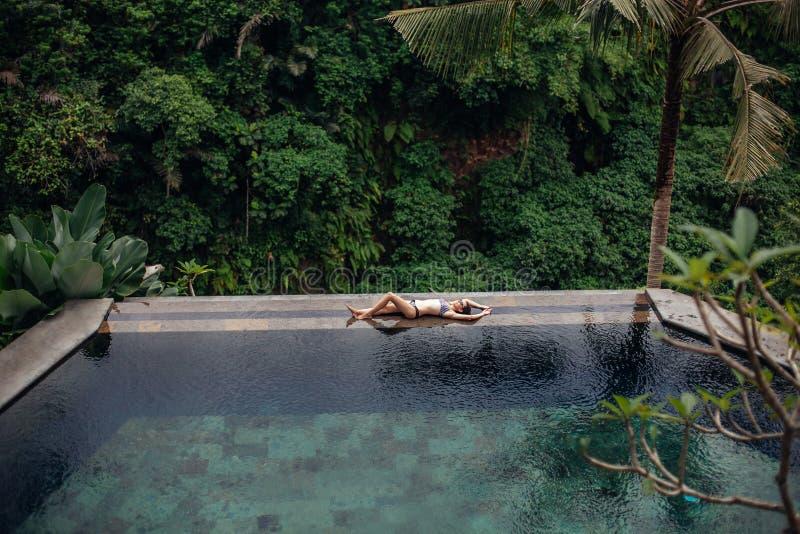 Nehmen Sie sexy Brunettefrau im Badeanzug ab, der auf tropischem Unendlichkeitspool des Randes im Dschungel sich entspannt Palmen lizenzfreie stockfotos