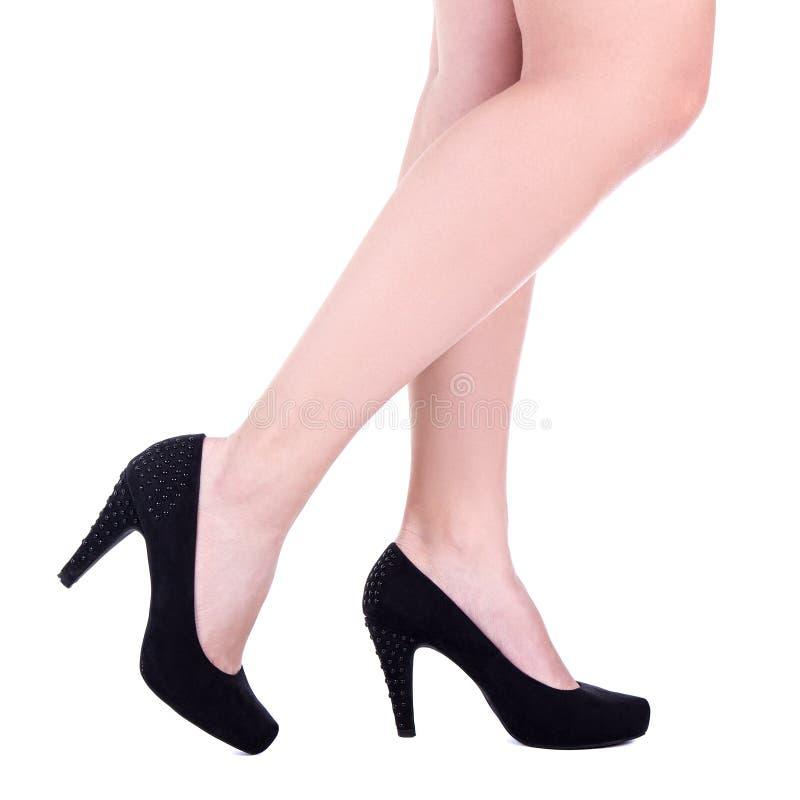 Nehmen Sie weibliche Beine in den schwarzen Samtschuhen ab, die auf Weiß lokalisiert werden lizenzfreies stockfoto