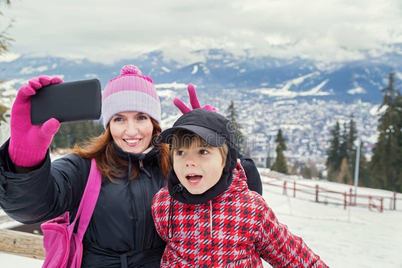 Nehmen von selfie! Familie Glückliche Mutter und kleiner Junge, die Selbstporträt in den Winterbergen macht stockbild