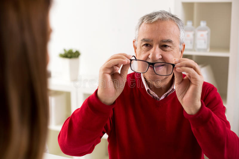 Nehmengläser aftere Änderung des älteren Mannes geduldige von Diopter lizenzfreie stockfotografie