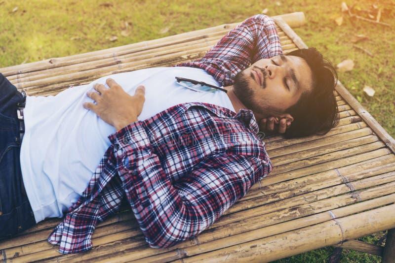 Nehmenhaar des jungen Mannes auf Bambusbett oder Sitz lizenzfreie stockfotografie