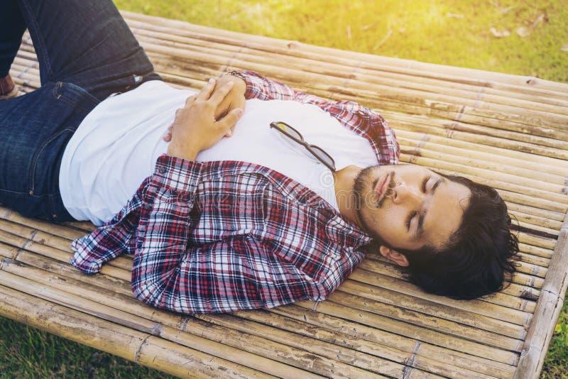 Nehmenhaar des jungen Mannes auf Bambusbett oder Sitz lizenzfreie stockfotos