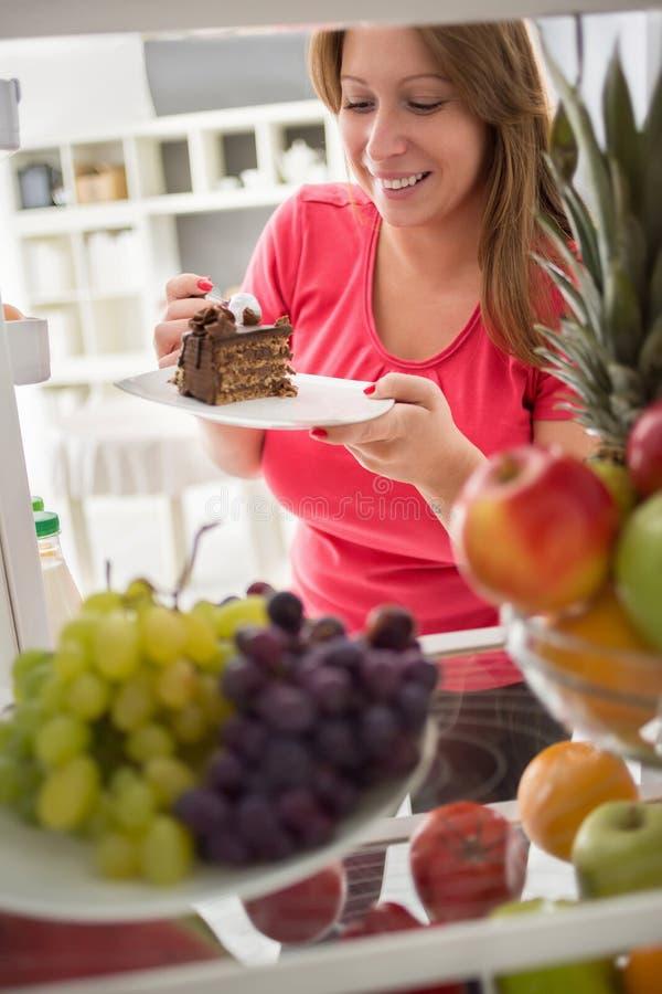 Nehmenstück der jungen Frau des Schokoladenkuchens vom Kühlschrank stockbild