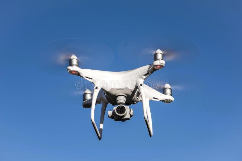 NEIDLINGEN, GERMANIA - 24 FEBBRAIO 2019: Vista frontale volo del fuco del quadcopter del fantasma 4 di DJI di PRO sul cielo blu fotografie stock libere da diritti
