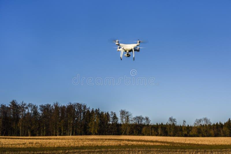 NEIDLINGEN, GERMANIA - 24 FEBBRAIO 2019: Vista frontale volo del fuco del quadcopter del fantasma 4 di DJI di PRO sul cielo blu fotografia stock libera da diritti
