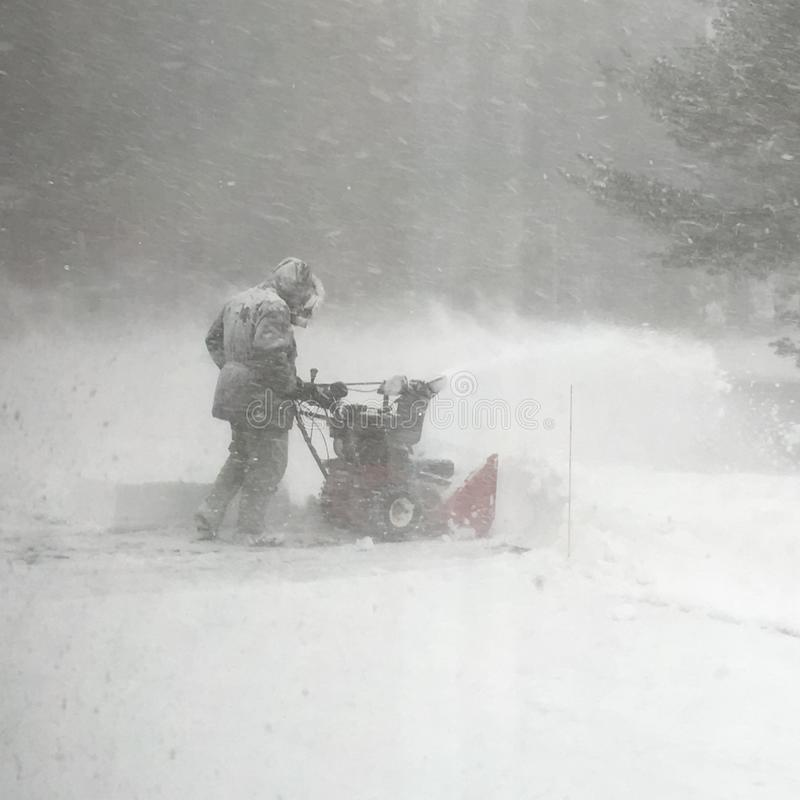 Neige de clairière d'homme pendant une tempête de neige images stock