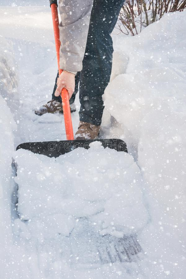 Neige de dégagement d'homme par la pelle après des chutes de neige outdoors photo stock