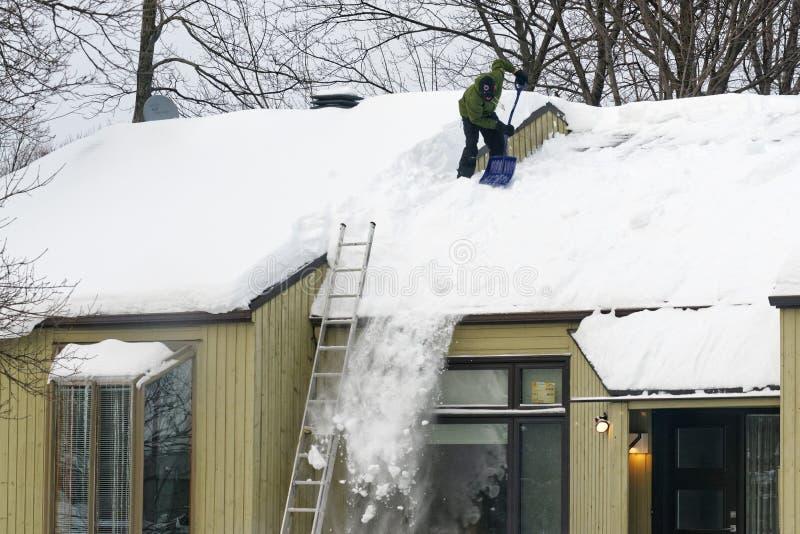 Neige de dégagement d'un toit au Québec photographie stock libre de droits