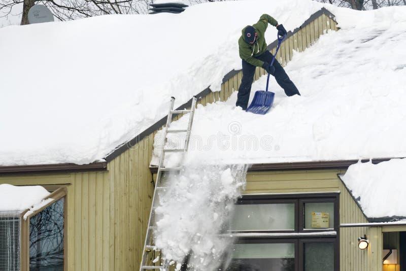 Neige de dégagement d'un toit au Québec photographie stock