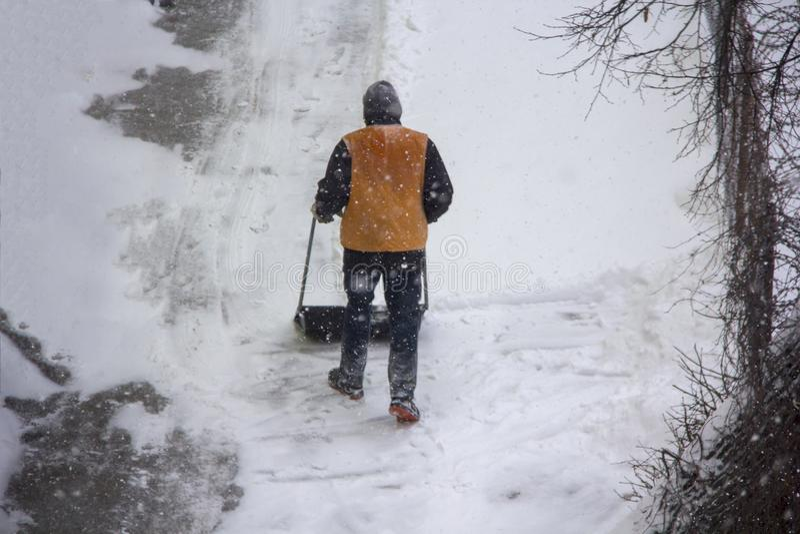 Neige de grippage de portier de gardien de yard avec une pelle sciene de neige d'hiver images libres de droits