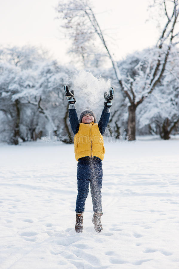 Neige de lancement sautante de garçon près de la forêt photo libre de droits