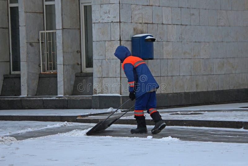 Neige de nettoyage de portier sur le trottoir avec une pelle photo libre de droits