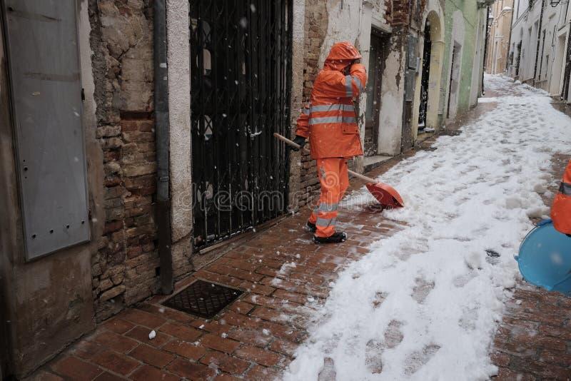 Neige de pelle à travailleurs au centre historique photographie stock libre de droits
