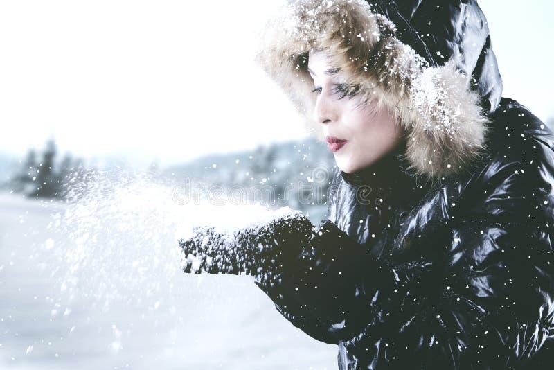Neige de soufflement de belle femme des mains photo stock